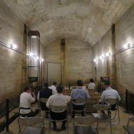 高い天井が特徴的な巨大防空壕シアター。正面奥のコンクリート壁面に映像が映し出される=加西市鶉野町